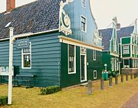 Sign for Dutch Watch and Clock Museum and row of historic wooden buildings, Zaanse Schans, Zaanstad, north Holland, Netherlands. Zaanse Schans is a UN...