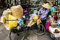 Street vendor selling peanuts from her bicycle in Hanoi, northern Vietnam.
