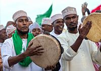 Sunni muslim men playing tambourines during the Maulidi festivities in the street, Lamu County, Lamu Town, Kenya.