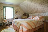 Queen size bed and furnishings in the upstairs guest room of an Old Canadiana (circa 1741) cottage style wooden siding Residential Home, Lanaudiere, Q...