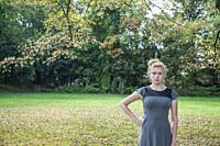 Blonde teenage girl standing outdoors.