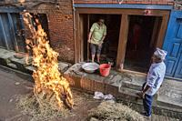 Cooking a goat in straw for the celebration of the Dasain holiday, Bhaktapur, Nepal.