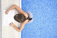 Child girl doing holidays homework over swimming poolside. Summer homework concept for children.