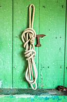 Rope hangs on wall of shed with chipping green paint, Cambridge, Maryland. USA.