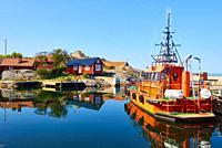Orange pilot boat in Vasterhamn (west harbour) on the island of Oja (Landsort), the southernmost point in the Stockholm archipelago, Sweden, Scandinav...