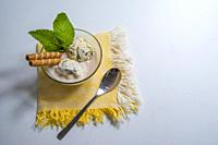Ice cream with biscuits and mint leaves.