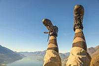 Hiking Shoes and Legs Up in the Air Over Alpine Mountain Range and Lake maggiore in Ticino, Switzerland.