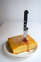 Cake stabbed by a kitchen knife.