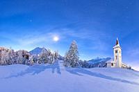 Moonlight on Chiesa Bianca surrounded by snow, Maloja, Bregaglia Valley, Canton of Graubunden, Engadin, Switzerland.