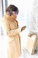 Woman with Overcoat and Scarf Using Smart Phone.