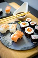 Sushi on a wooden table on black slate plate with soy sauce and chopsticks.