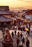 Matsubara dori street at sunset in autumn, busy with tourists and visitors at the entrance to Kiyomizu-dera Buddhist temple. Higashiyama, Kyoto, Japan...