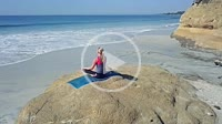 Circling a young woman sitting on a rock meditating and practicing yoga