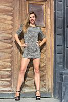 Sexy and elegant Ukrainian woman wearing a leopard skin print dress posing standing in front of a large wooden door for a photographic sequence in the...