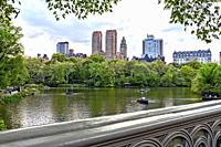 Central Park, Manhattan, New York City. Looking Over the Lake to Central Park Weet Skyline from Bow Bridge. People i Rowboats on the Lake.
