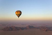 The hot-air balloon above an arid plain and isolated mountain ridges at the edge of the Namib Desert. Aerial view from a second balloon. NamibRand Nat...