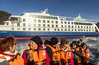 Ventus cruise ship passengers ride Zodiac to disembark and explore Ainsworth Bay, in background Ventus cruise ship,Tierra del Fuego, Patagonia, Chile.