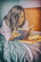 Young Hispanic woman, lying on a bed, reading a book.
