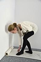 A woman artist bends over to draw on rolled paper as part of a performance art work at an artist run gallery in Windsor, Canada. Her art involves repe...