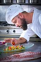 Chef garnishing flower in ceviche dish with hands at stainless steel kitchen.