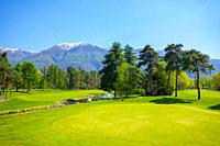 Hole 8 in Golf Club Ascona with Trees and Mountain in Ticino, Switzerland.
