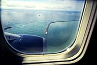 View from airplane window. View of containership leaving the port of Barcelona. Barcelona, Catalonia, Spain.