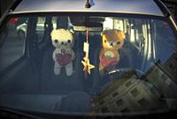 Interior of a car with two dolls seen from the front window with reflections in the glass. Mahon, Menorca, Baleares, Spain.