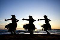 Three hula dancers at sunset at Wailea, Maui, Hawaii.