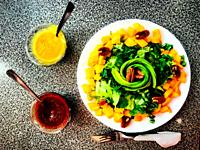 A salad with lettuce, mango, nuts and avocado a spicy red sauce and mustard sauce in a organic healthy food restaurant in Coyoacan, Mexico City, Mexic...
