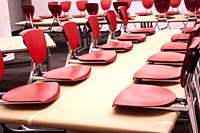 Orange plastic and metal children´s chairs placed on a table top in a classroom creating a graphic design.