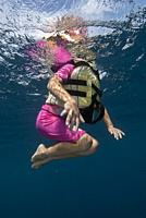 Girl (model released) with life jacket floating in sea, Tulamben, east Bali, Indonesia.