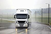 White cargo truck transports goods along wet road on rainy day in summer.