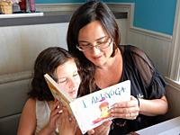 Mother and Daughter Reading Book Together, Perry, New York, USA.