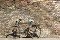 Old styled bike abandoned against an old brick wall, back streets, Bruges, Belgium.