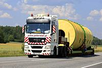 Wide load transport of a silo by MAN TGX 26. 540 semi trailer of Peter-Star, Poland on the road in South of Finland. Salo, Finland - July 27, 2018.
