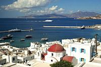 View to a red domed church in town center with a speed ferry entering the harbour at the background, Mykonos, Cyclades Islands, Greek Islands, Greece,...