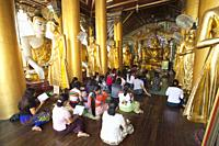 Devotees prying in a temple in the Shwedagon pagoda, Yangon, Myanmar, Asia.