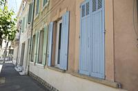 Neapolitan ice cream coloured shutters in pale shades on a warm terracotta building on a tree lined street in Salon, Provence, France.