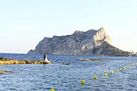 Wedding couple embraced in the middle of the Mediterranean Sea and in the background the Peñon de Ifach, Calpe, Alicante, Valencia, Spain