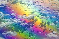 Aerial view of clouds below, at 10,000 meters, photographed from a regular commercial flight. The rainbow of colours is due to light refraction.