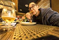 man eating with chopsticks in Valencia, Spain