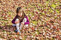 Five year old girl playing with an autumn leaf.