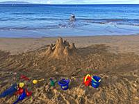 A man wades into the water while a castle and tools are strewn about on the sand, sand, Charley Young Beach, S. Kihei, Maui, Hawaii, USA.
