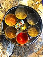 Colorful combination of seven essential spices used in North Indian cooking in a round container on a granite counter.