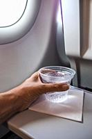 Hand holding a plastic cup with sparkling water inside an airplane.