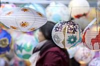 Seattle, Washington: Woman browses at the Lantern Shoppe at the Aqua Theater before the Luminata Lantern Parade. Hand-decorated lanterns are sold as a...