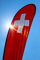 Swiss Banner Flag with Sunlight and Against Blue Sky in Switzerland.