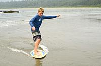 Teenage boy skim boarding on Flores Island, off the west coast of Vancouver Island, British Columbia, Canada.