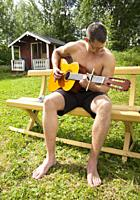 Young man playing guitar on holiday