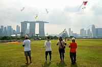 29. 07. 2018, Singapore, Republic of Singapore, Asia - People are seen flying kites on the Marina Barrage rooftop garden. The Marina Bay Sands Hotel i...